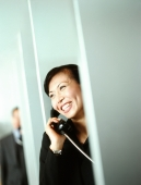 Woman executive using public telephone, male executive in background. - Jack Hollingsworth