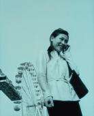 Woman on cellular phone, ferris wheel in background. - Jack Hollingsworth