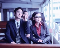 Male executive on cellular phone with female next to him, outdoors. - Jack Hollingsworth