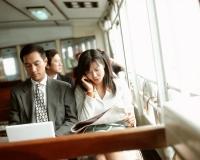 Male executive using laptop, female using cellular phone, outdoors. - Jack Hollingsworth