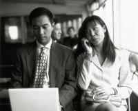 Male executive on laptop, female on cellular phone. - Jack Hollingsworth
