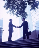Executives shaking hands at top of stairs, buildings in background. - Jack Hollingsworth