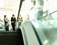 Executives on escalator talking. - Jack Hollingsworth