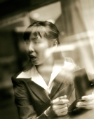Female executive using PDA seen through glass window. - Jack Hollingsworth
