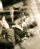 Female executives using PDA and cellular phone seen through glass window. - Jack Hollingsworth