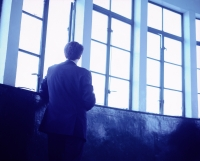 Executive with back to camera looking out window. - Jack Hollingsworth
