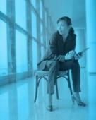 Female executive holding PDA sitting by window. - Jack Hollingsworth