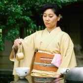 Japan, Woman in kimono performing outdoor tea ceremony - Rex Butcher