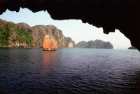 Vietnam, Halong Bay, Fishing junk amongst the islands viewed from a cave - Gareth Jones