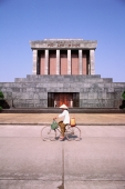 Vietnam, Hanoi, woman cycling past Ho Chi-Minh's mausoleum - Gareth Jones