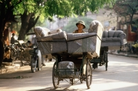 Vietnam, Hanoi, man delivering armchairs on cyclo - Gareth Jones