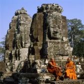 Cambodia, Angkor Thom, monks sitting at foot of Face towers, the Bayon - Gareth Jones