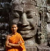 Cambodia, Ankor Thom, portrait of monk in front of the face of Avalokitesvara - Gareth Jones