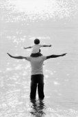 Father and son wading in water, son on father's shoulders, arms stretched - Jade Lee