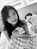 Woman clutching pillow, man sleeping in background, portrait - Jade Lee