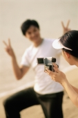 Couple at beach, woman filming man making peace sign - Jade Lee
