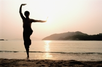 Silhouette of man doing Kung Fu moves at beach - Jade Lee