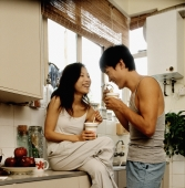 Couple eating instant noodles in kitchen - Jade Lee