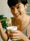 Man eating instant noodles - Jade Lee