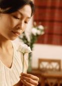 Woman looking at flower, dining room in background - Jade Lee