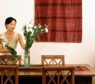 Woman arranging flowers in dining room - Jade Lee