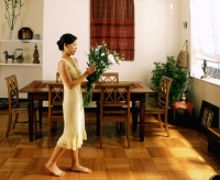 Woman holding flowers, walking in dining room - Jade Lee