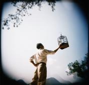 Man holding up birdcage - Jade Lee