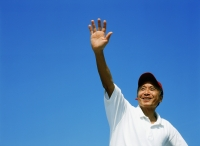 Mature man with red cap, waving, blue sky - Jade Lee