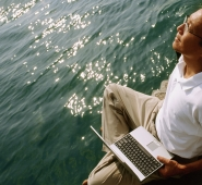 Man holding laptop, water in background - Jade Lee