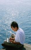 Man using laptop, sea in background - Jade Lee