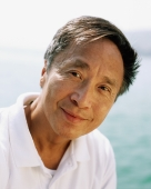 Mature man outdoors, sea in background, portrait - Jade Lee