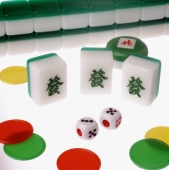 Mahjong tiles, dice and chips on a lit table - Gareth Brown