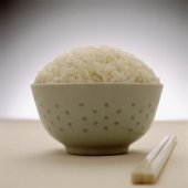 Full bowl of rice with chopsticks in foreground - Gareth Brown