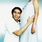 Man listening to stomach of pregnant woman - Erik Soh