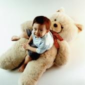 Young boy sitting on teddy bear - Erik Soh