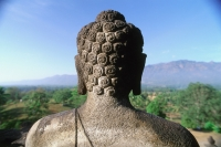 Indonesia, Java, Buddha figure at Borobudur temple, mountains in background - Jill Gocher