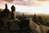 Indonesia, Java, Buddha figure at Borobudur temple at dawn,  mountains in background - Jill Gocher