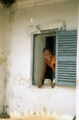 Laos, Luang Prabang, Young monk looking out of window at monastery - Jill Gocher