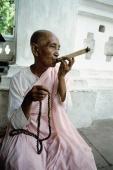 Myanmar, Mandalay area, Nun smoking cigar while holding prayer beads - Jill Gocher