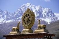 China, Szechuan (Sichuan), Kham region, Buddhist icon with mountains in background. - Jill Gocher