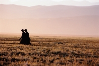 China, Szechuan (Sichuan), Kham region, Tibetan monks walk along the grasslands in the early morning. - Jill Gocher