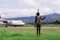 Indonesia, Irian Jaya, Dani warrior, modern plane in background - Jill Gocher