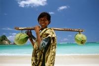 Indonesia, Lombok, boy selling coconuts on beach - Jill Gocher