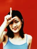 "Young woman with finger and thumb in shape of ""L"" on forehead, red background. - Jack Hollingsworth"
