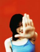 Young woman with hand extended out front, red background. - Jack Hollingsworth