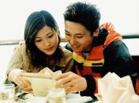 Young couple looking at menu at restaurant. - Jack Hollingsworth