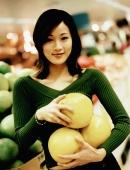 Young woman holding fruit, portrait. - Jack Hollingsworth