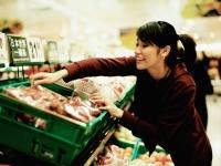 Young woman at supermarket choosing fruit. - Jack Hollingsworth