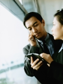 Executives using PDA and cellular phone. - Jack Hollingsworth