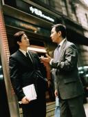 Executive pair talking on street. - Jack Hollingsworth